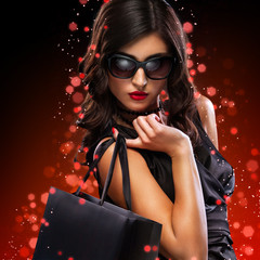 Christmas and Black friday sale concept. Shopping woman holding grey bag isolated on dark background in holiday
