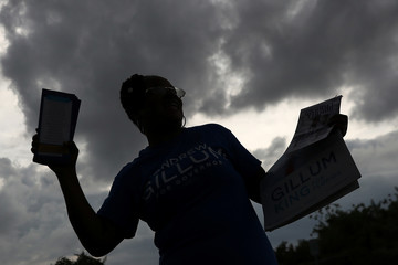 """A supporter of Democratic gubernatorial candidate Andrew Gillum dances in silhouette during a """"Vote with Gillum"""" party at an early voting site in Boynton Beach, Florida"""