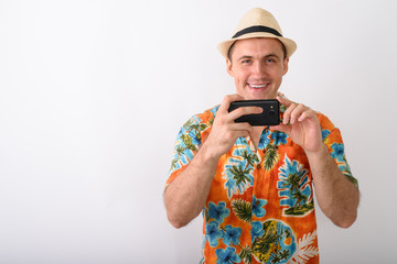 Studio shot of young happy muscular tourist man smiling while ta