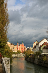 View of Ljubljanica river in old city with dark stormy clouds in the background on an autumn day, Ljubljana, Slovenia