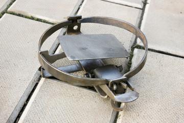 One rusty iron trap lying on stone floor