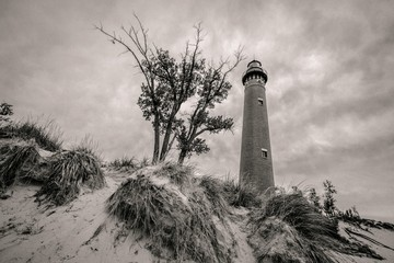Abstract Lighthouse Background. Black and white lighthouse towers over a sand dune on the shores of Lake Michigan. Little Sable Lighthouse in Silver Lake State Park, Michigan.