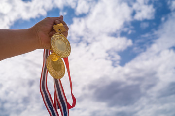 Winner hand raised holding two gold medals with Thai ribbon against blue sky. Golden medals is award for highest achievement for sport or business. Success Awards concept