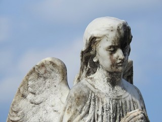 Stone statue of an angel with wings, praying. Statue damaged by time. In the background, the blue sky. Peace and faith.