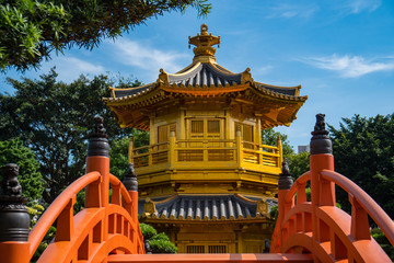 Golden Pagoda with a Chinese and Japanese style roof surrounded by green trees. calm, zen, peaceful garden in Hong Kong
