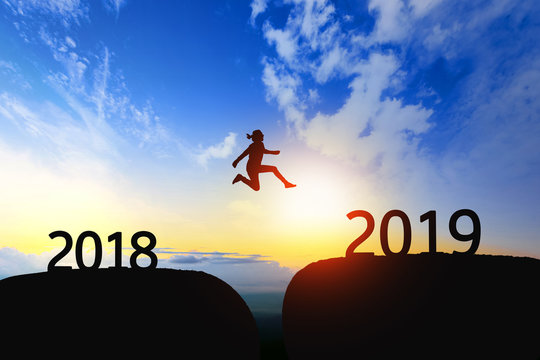 Woman jump through the gap between 2018 to 2019 on sunset.