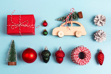 Set of Christmas decorations on blue background. Wooden toy car with Christmas tree on the roof, gift box and other baubles.