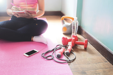 Sporty and healthy young woman planning for dieting. Exercise and workout