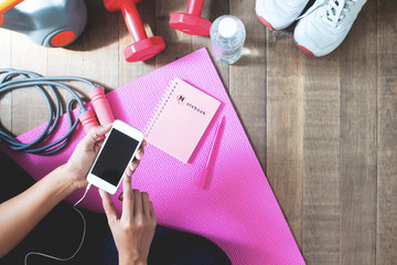Top view of woman using mobile phone for online fitness training with fitness equipments on wooden floor