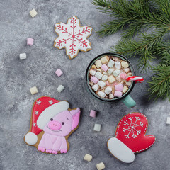 Christmas Gingerbread. Symbol of Year - Cute Pig, Snowflake and Mitten with Cup of hot cocoa with marshmallows on a gray stone concrete table background. Top view with copy space, flat lay