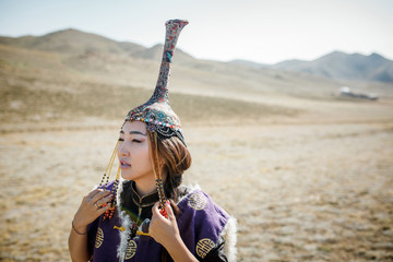 Portrait tuvan girl in national dress in the steppe with national yurt