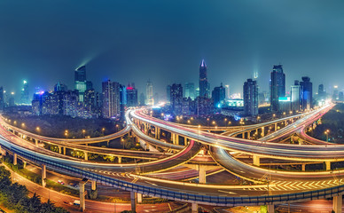 View on famous highway intersection in Shanghai, China, with illuminated highways and skyscrapers.