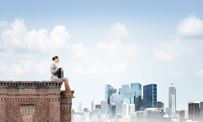 Businesswoman or accountant on brick roof against modern city scape