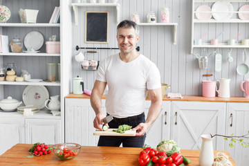 Portrait of handsome smiling man chopping vegetables in the kitchen. The concept of eco-friendly products for cooking.