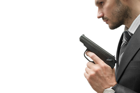 A man in a jacket holds a gun in his hand. Focus on the gun.