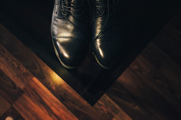 A pair of black leather shoes on a dark background