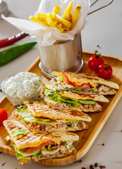 Skepasti: pork gyros with meat, tzatziki sauce, vegetables, cheese and french fries on wooden plate