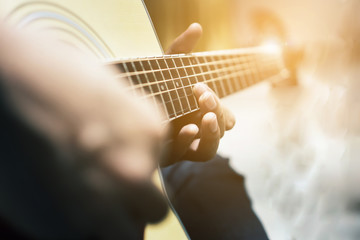 The man is playing guitar in the garden, Close-up male hand playing on acoustic guitar outdoor with bokeh and rays of sunlight.