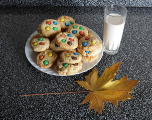cookies with M & M's in a white plate, a glass of milk and a maple leaf on  kitchen table