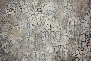 an old concrete wall with a lot of black cracks. cracked surface of the concrete wall. rough texture.