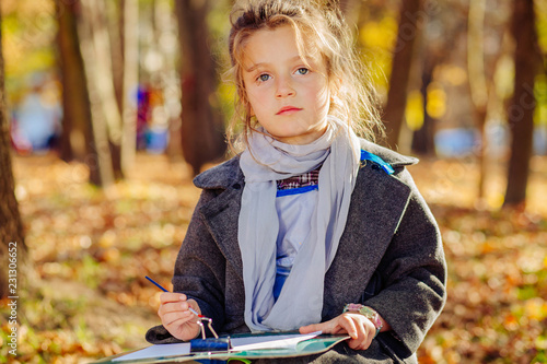 f7084ee9b1551 Portrait of cute little french girl in coat and scarf paitner artist  drawing with brush and paint over fall autumn leaves park background.