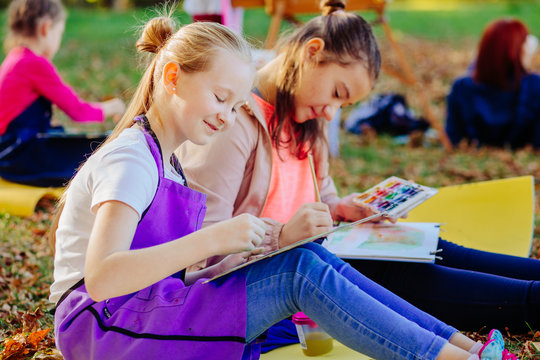 Two teenagersartist girls sitting on park and painting with crayon pencil outdoor. Creative children painting on nature sitting on ground. Activity for kids concept.