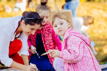 Young attractive mother teaches children painting in autumn park. Creative child painting on nature sitting on ground. Outdoors activity for school age children concept