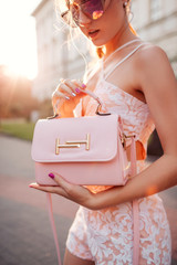 Fashionable woman in stylish outfit holding beautiful handbag and wearing sunglasses outdoors.