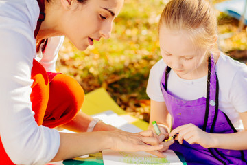 Young attractive mother teaches daughter painting in autumn park. Outdoors activity for school age children concept