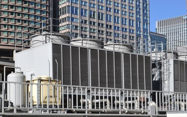 Cooling tower for HVAC system with coils and fins on display with backdrop on city buildings
