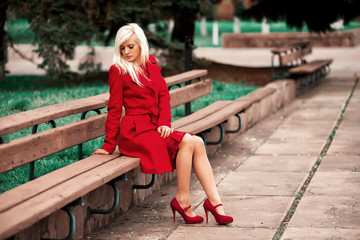 Woman in red coat and shoes sitting on a bench in the park