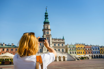 Woman photographing Old Town of Zamosc, Poland