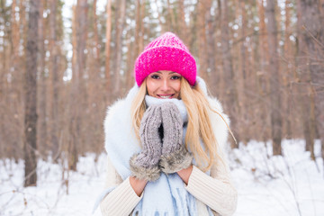 Season and people concept - Attractive blond woman dressed in white coat and pink hat standing in winter snowy park