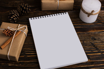 Notepad and gift on the wooden table. Place for text. Copy space.