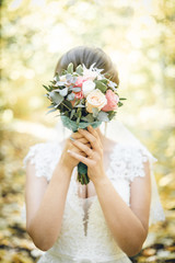 Beautiful bride with bridal bouquet. woman in autumn park. bride covers face with a bouquet. bouquet instead of face