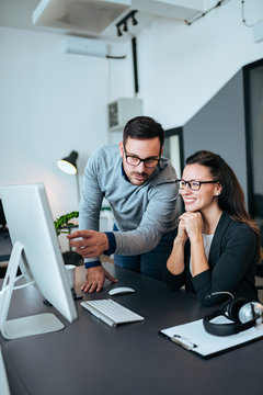 Two confident young business people looking at computer monitor. He is pointing at something.