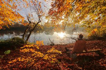 Mann sitzt auf einer Bank in herrlicher Herbst Landschaft