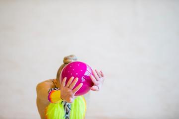 Girl with a rhythmic gymnastics pink ball. Flexibility in acrobatics and fitness health