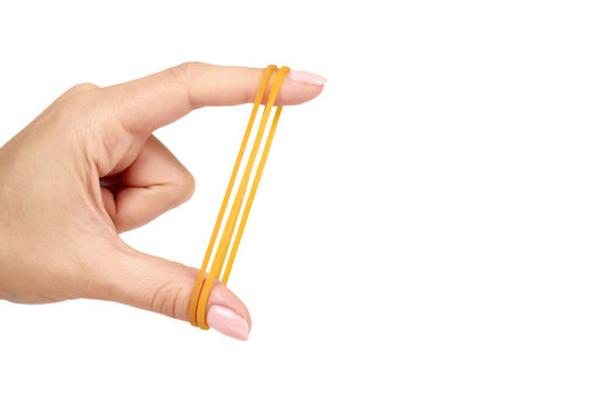 Yellow rubber bands close up with hand isolated on white background, copy space template.