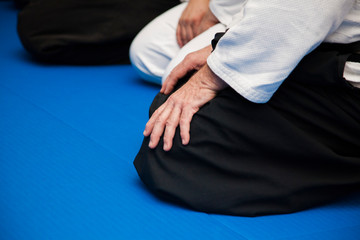 Aikido athletes in kimono sit on blue tatami at the beginning of training