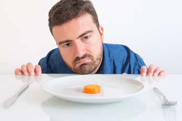 Depressed man dieting and eating only vegetables