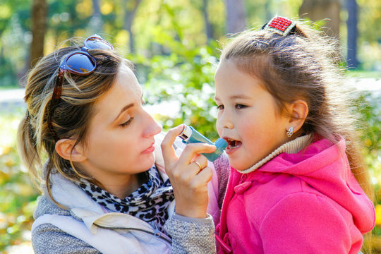 caring mom helps girl to use an inhaler against asthma