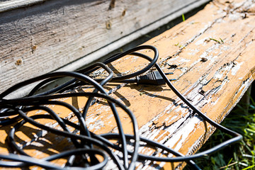 Black wire with plug on a wooden bench