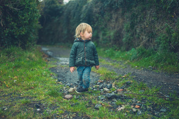 Toddler standin in the countryside on gravel road