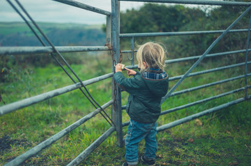 Little toddler standing by fence in the countryside