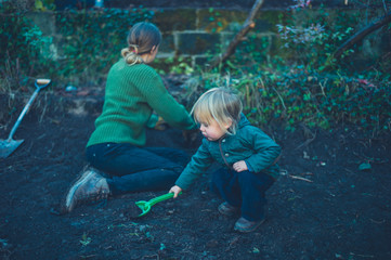 Mother and toddler working in garden in autumn