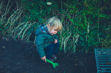 Toddler standing in garden with toy spade