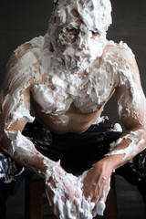 photo portrait of a muscular guy smeared with shaving foam sitting and leaning forward