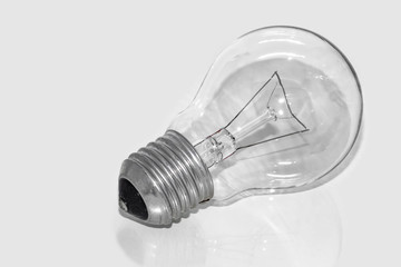 An old glass transparent incandescent lamp is on a white