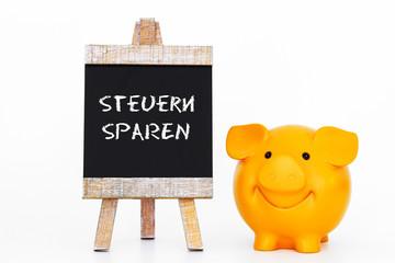 Steuern sparen Sparschwein mit Tafel